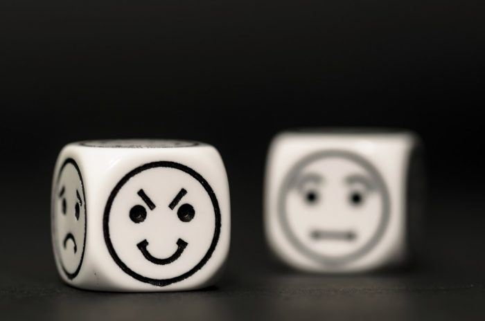 emoticon dice with cunning and confused expression sketch on black background - stock photo